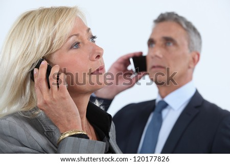 businessman and businesswoman talking on their cells - stock photo