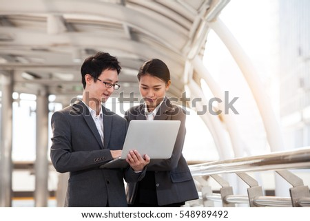 Businessman and businesswoman using digital laptop computer at Outside Office, Success and Happiness Team Concept.