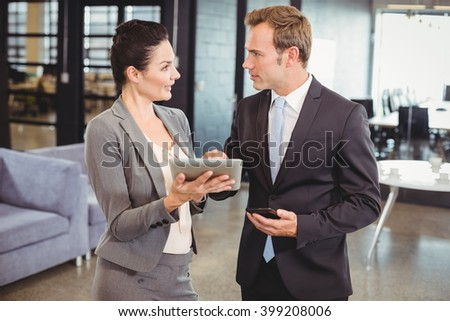 Businessman and businesswoman using digital tablet in office - stock photo