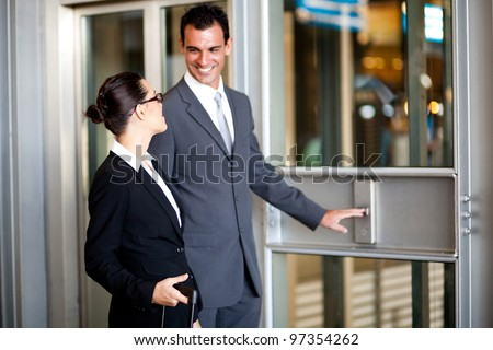 businessman and businesswoman using elevator at airport - stock photo