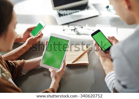 Businessman and businesswoman using touchpad and smartphones - stock photo