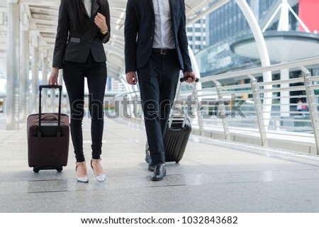 businessman and businesswoman walk together with luggage on the public street, business travel
