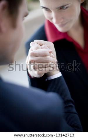 businessman and businesswoman wearing suits sit as they arm wrestle - stock photo