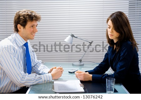 Businessman and businesswoman working together in team at office, smiling. - stock photo