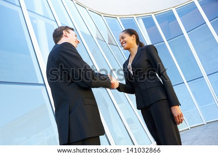 Businessman And Businesswomen Shaking Hands Outside Office - stock photo
