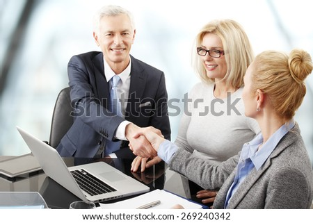 Businessman and businesswomen sitting in front of laptop at the table and shaking hands. Group of business people sitting at business session.  - stock photo