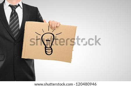businessman and cardboard with lamp symbol - stock photo