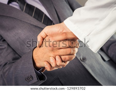 Businessman and doctor shaking hand's. - stock photo