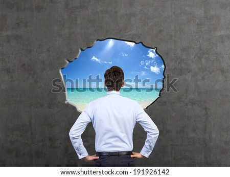 Businessman and dreams about vacation, hole in a wall. - stock photo