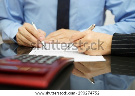 businessman and female coworker are examining financial agreement - stock photo