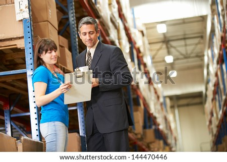 Businessman And Female Worker In Distribution Warehouse - stock photo