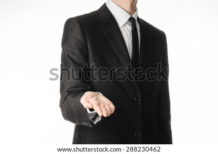 Businessman and gesture topic: a man in a black suit and tie holds out his hand isolated on a white background in studio