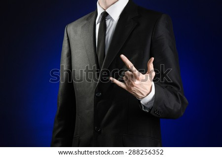 Businessman and gesture topic: a man in a black suit and white shirt shows a hand sign rock on a dark blue background in studio isolated - stock photo