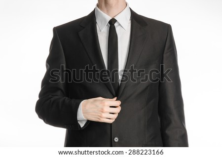 Businessman and gesture topic: a man in a black suit with a tie coat straightens his arms isolated on a white background in studio
