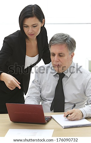 Businessman and his assistant at his desk n front of a laptop