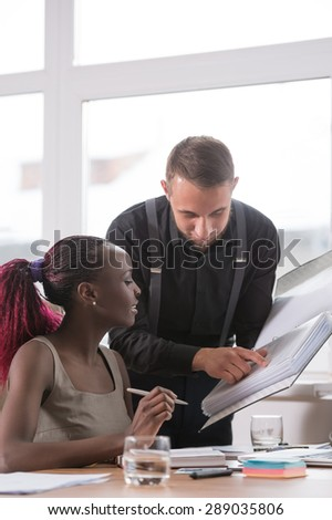 Businessman and his colleague at office working together - stock photo