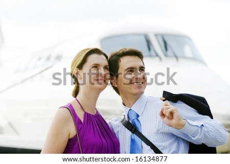Businessman and his wife expect boarding on plane - stock photo