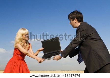 businessman and lady in red fighting for notebook