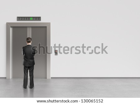 businessman and modern elevator with closed doors - stock photo