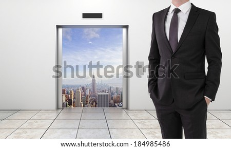 businessman  and modern elevator with opened door to city - stock photo