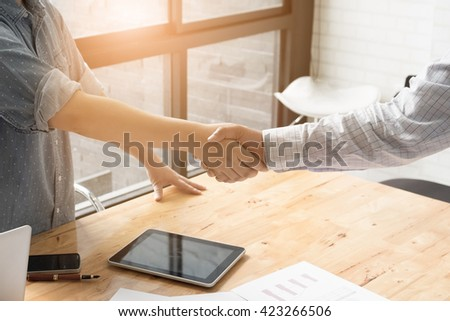 Businessman and partner shaking hands in office - stock photo