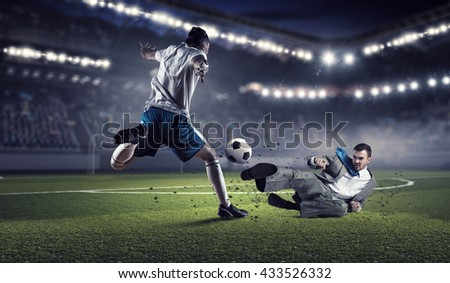 Businessman and player fighting for ball