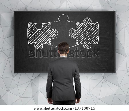 Businessman and two pieces of puzzle connected by third.  - stock photo
