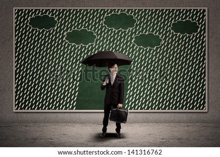 Businessman and umbrella with copy space under the rain - stock photo
