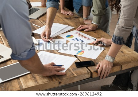 Businessman and woman discussing on stockmarket charts in office  - stock photo