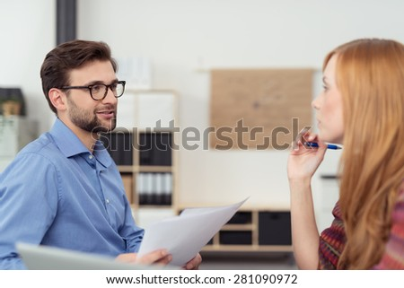 Businessman and woman having a meeting sitting facing each other discussing paperwork with serious expression, focus on the man - stock photo