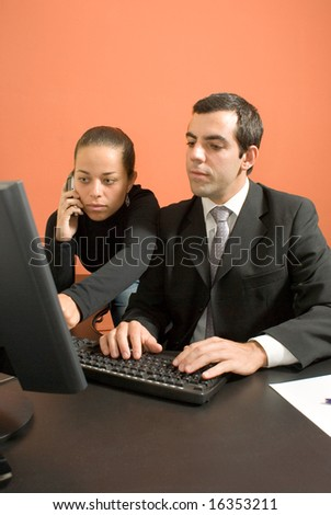 Businessman and woman hover over a computer - stock photo