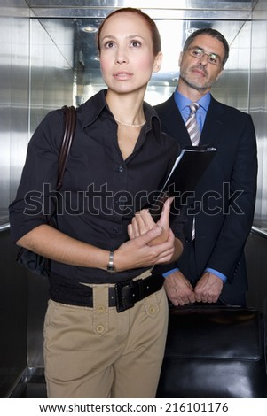 Businessman and woman in elevator - stock photo