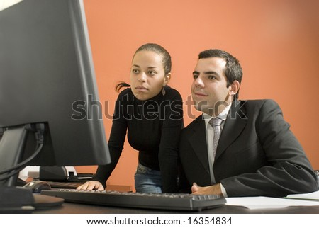 Businessman and woman looking at a computer. Horizontally framed photo. - stock photo