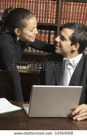 Businessman and woman smiling at each other surrounded by books and a laptop. Vertically framed photo. - stock photo