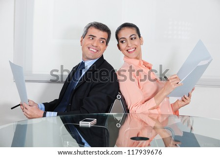 Businessman and woman spying in each others files in the office - stock photo