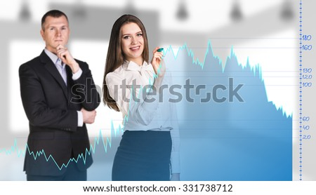 Businessman and woman stands behind the big graph on the office background.