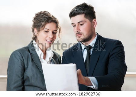 Businessman and woman talking over a notebook - stock photo