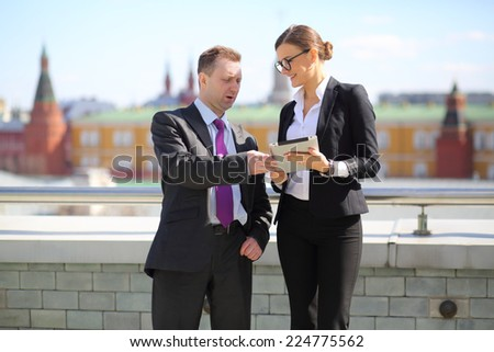 Businessman and woman with tablet computer talking on the terrace overlooking Kremlin