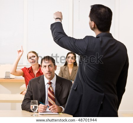 Businessman answering questions in meeting - stock photo