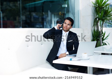 Businessman answering the phone with a smile, receiving good news, asian businessman having a phone talk, attractive rich man using mobile phone, emotions talking on the mobile smart phone  - stock photo