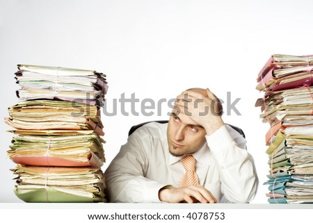 Businessman appears to be overwhelmed by his workload.  Stacks of files are on either side of him.  Isolated on white background. - stock photo