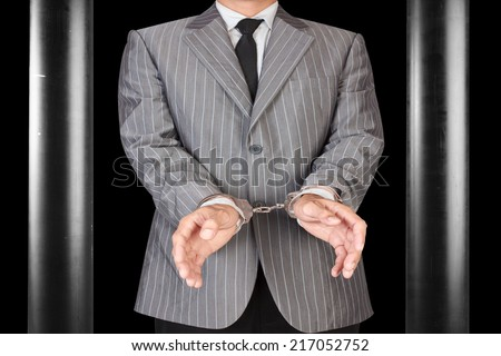 businessman arrested with handcuffs in dark jail  - stock photo