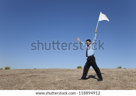 businessman asking for surrendering holding a white flag - stock photo