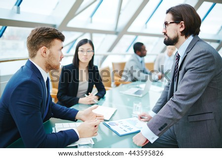 Businessman asking questions to leader at meeting