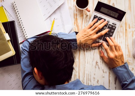 Businessman asleep at office desk with finance sheet calculator and coffee.(concept for overworked) - stock photo