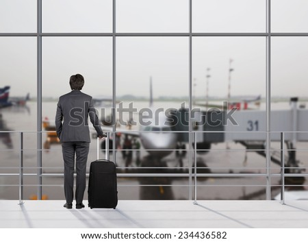 Businessman at airport with suitcase  - stock photo