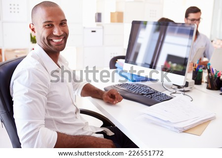 Businessman At Computer In Office Of Start Up Business - stock photo