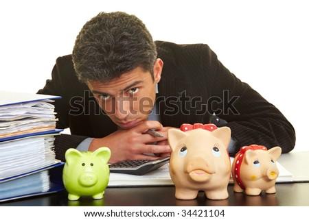 Businessman at his desk behind three piggy banks - stock photo