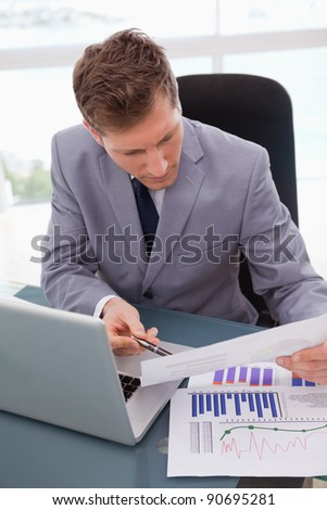 Businessman at his desk looking at statistics - stock photo
