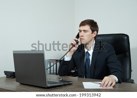 Businessman at his desk talking on the phone - stock photo